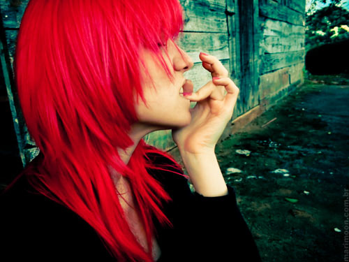 teenager with long red hair biting their nails in an allyway