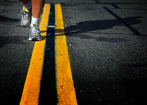Legs with running shoes running on the highway where the double yellow solid lines are.