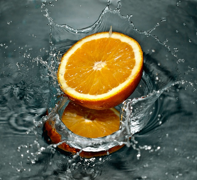 Half an orange splashing in water