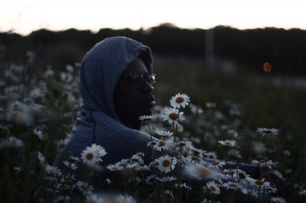 masculine presenting person with dark skin. They are sitting in a field of daisies